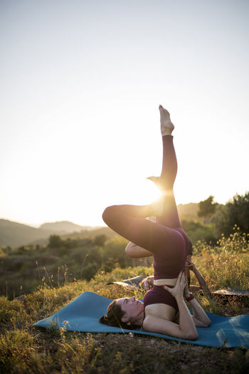 Women exercising on mats against clear sky at sunset