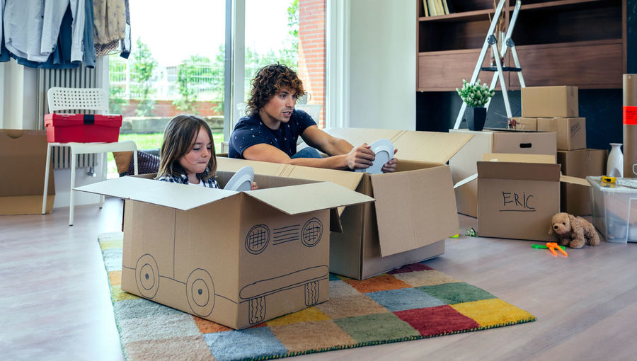 Father and son playing car racing with cardboard boxes in the living room Family Fun Funny Happiness Happy Horizontal Moving Unpacking Apartment Boxes Boy Cardboard Home Interior House Indoors  Lifestyles Living Room Mammal New Home Packing Placing Race Real People Relocating Two People