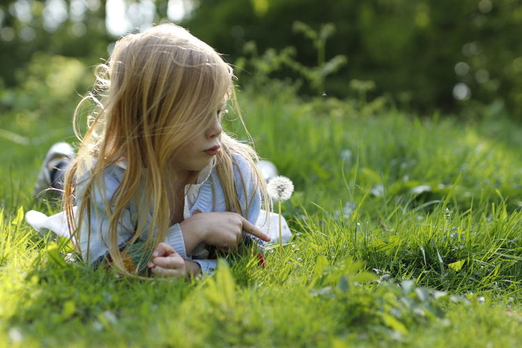 Girl sitting on grassy field