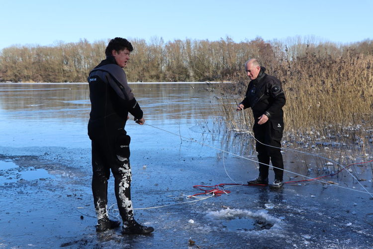 Full length of young man standing in lake during winter