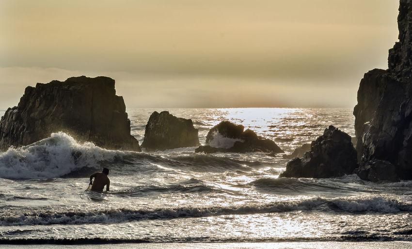 Man Swimming In Sea During Sunset