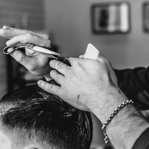 Cropped Image Of Hairdresser Hand Cutting Hair