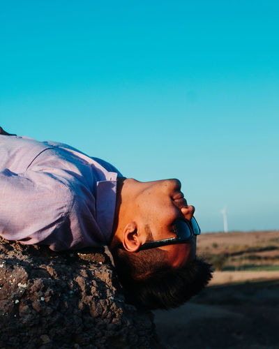 Young man in sunglasses lying outdoors against sky