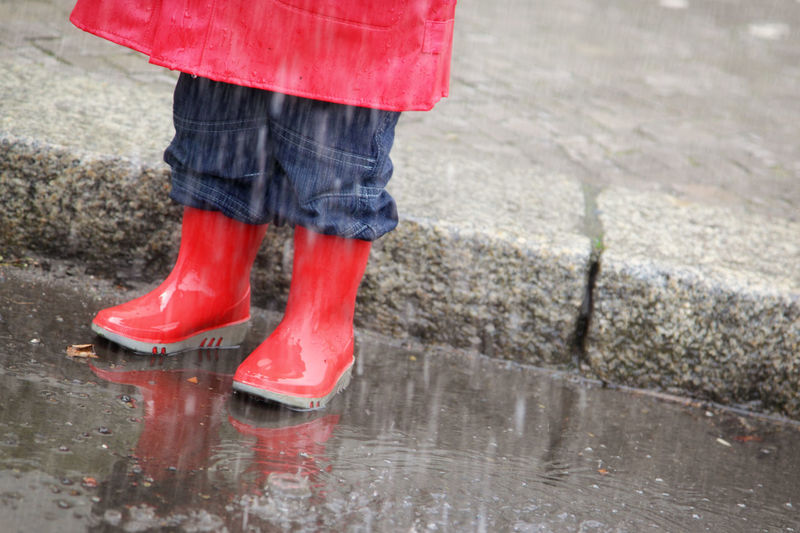 Low section of boy standing in puddle