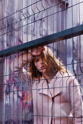 Portrait of teenage girl seen through railing