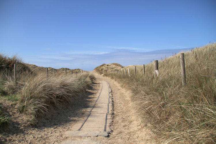Footpath Non-urban Scene Outdoors Grass Landscape Sky Direction The Way Forward No People Day Dirt Road Beauty In Nature Road Environment Nature Diminishing Perspective Scenics - Nature Sand Marram Grass Blue Sky Curved Path Sunlight Summer Travel Harlech Hill Wooden Pathway