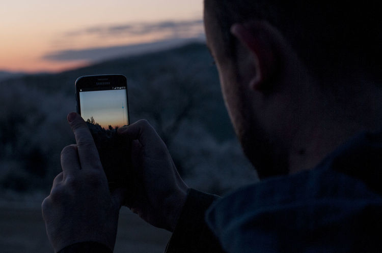 Wireless Technology Technology Communication Smart Phone Portable Information Device Mobile Phone Screen Activity Holding Sunset Photography Themes Device Screen Photographing Connection Sky Leisure Activity Human Hand People Hand Adult Outdoors