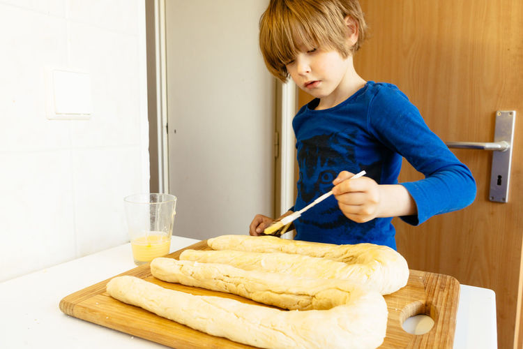 Brushing egg yellow yolk on dough, baking a sweet braid bread in a home kitchen. Baking Boy Bread Brush Brushing Caucasian Dough Egg Egg Yolk Home Home Made Loaf Preschooler Self Made Yellow