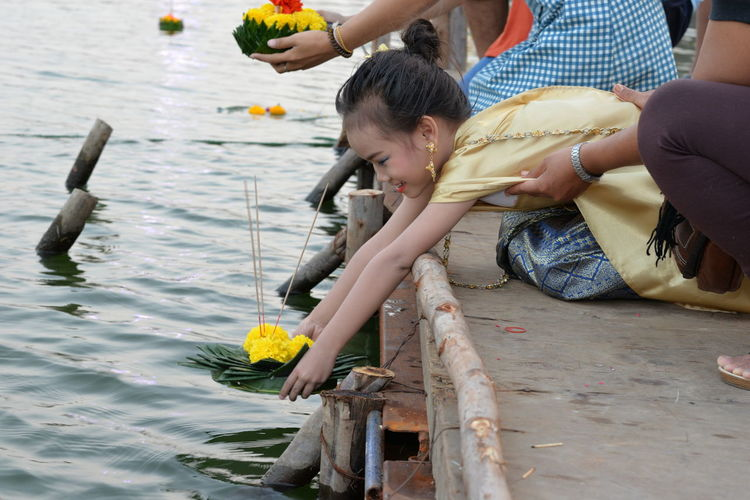 Girl with mother worshipping flowers and incense over lake