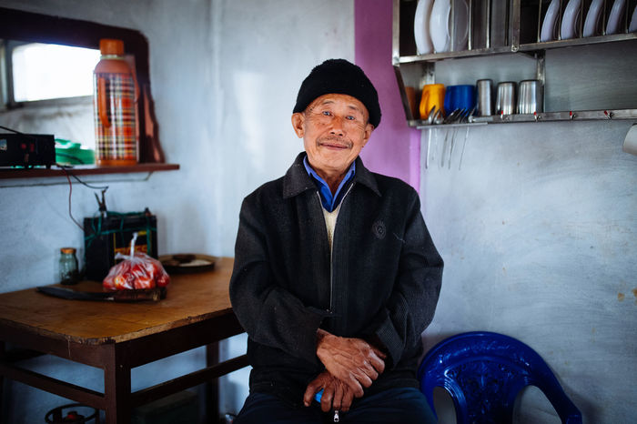 PORTRAIT OF A SMILING MAN SITTING AT HOME