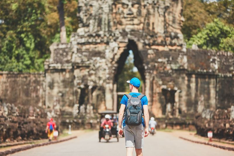 Rear View Of Young Man With Backpack Walking Towards Built Structure
