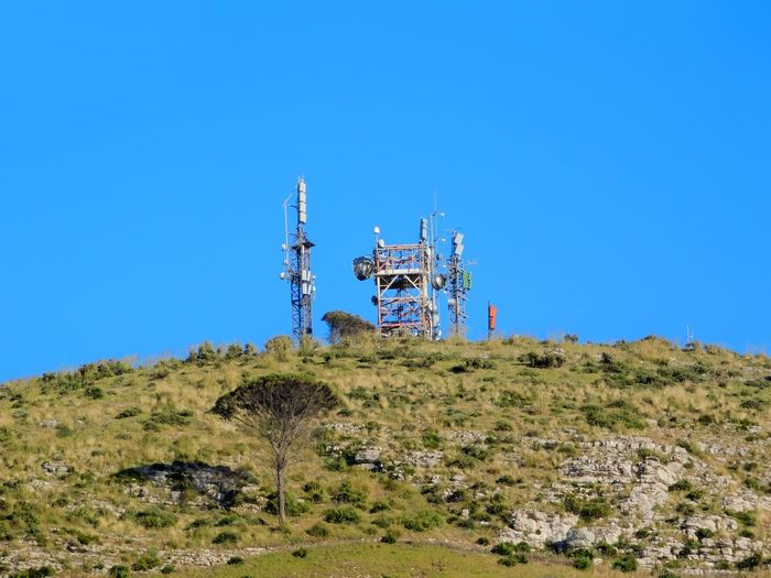 Low angle view of communication tower on hill against clear blue sky