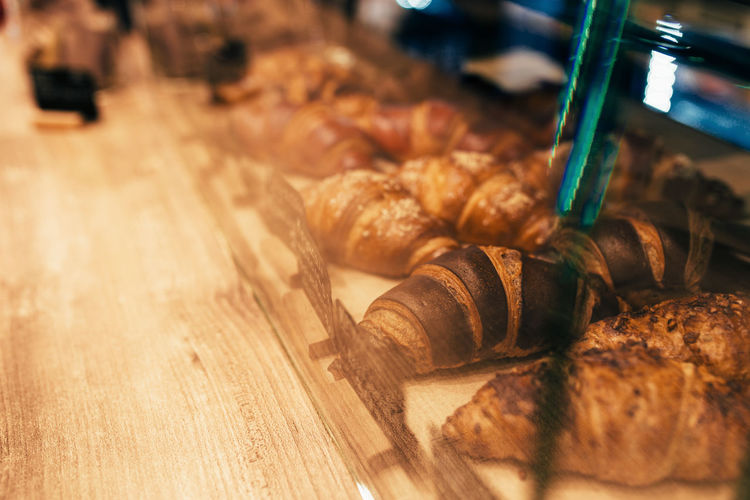 The waiter pulls out croissants in a cafe window. blurred background. high quality photo