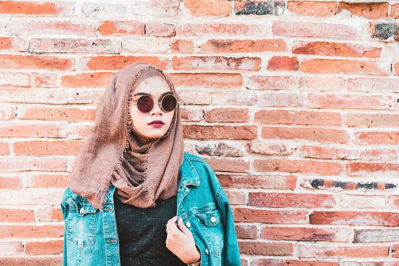 Portrait Of Woman Wearing Sunglasses Against Brick Wall