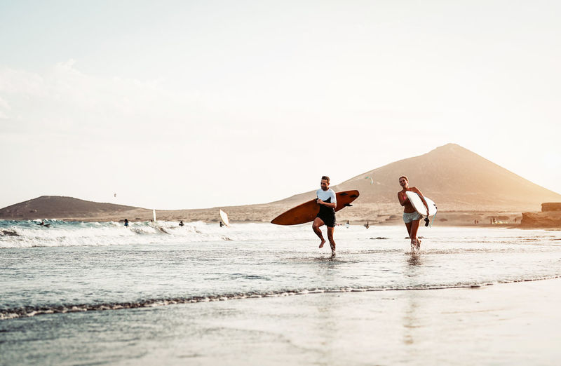 Man and woman running while holding surfboards at beach against sky