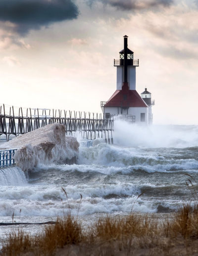 The beautiful St Joseph lighthouse stands strong against windy, cold waves, on the shores of Lake Michigan in February USA Wave Power In Nature Built Structure Stormy Weeather Architecture St Joseph Lighthouse Lighhouse Landmark Lake Michigan Landscape Michigan USA North America Great Lakes Motion Waves Water High Waves Cold Temperature Winter Windy Day February Outdoors Nature Beauty In Nature Sky