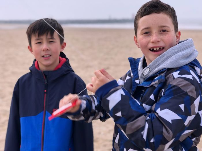 Portrait of boys standing on beach