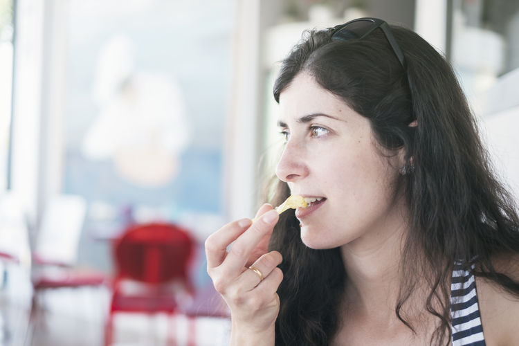 Mid adult woman eating potato chip at restaurant