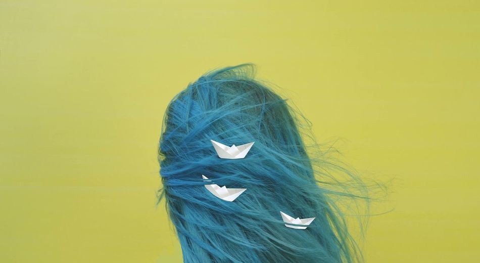 Rear view of woman with paper boats in dyed hair against yellow background