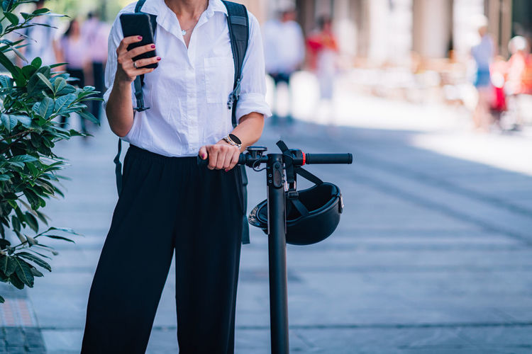 Midsection of woman using phone while standing with scooter on road