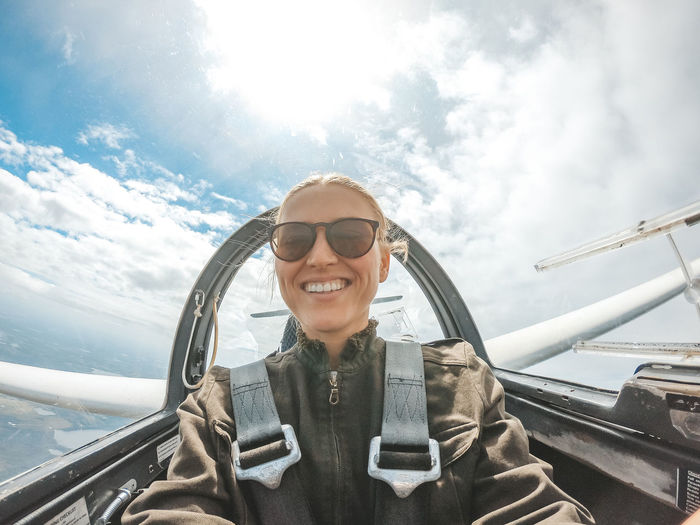 Portrait of woman flying airplane against cloudy sky