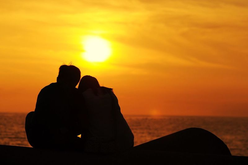 Rear view of couple sitting on coast against cloudy sky at dusk