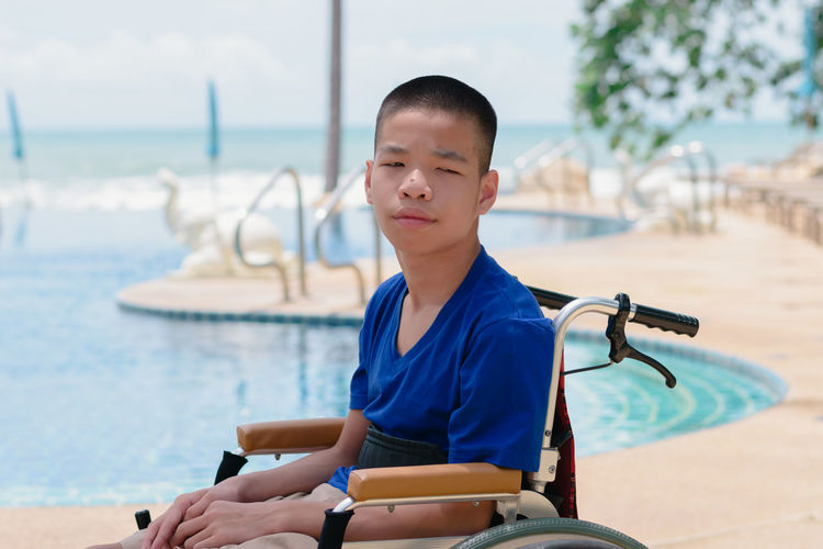 Portrait of boy sitting on wheelchair against swimming pool