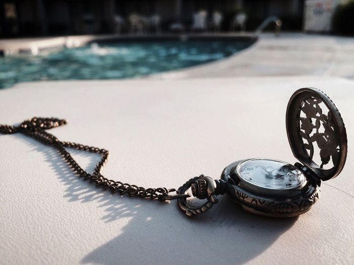Close-up of pocket watch at poolside during sunny day