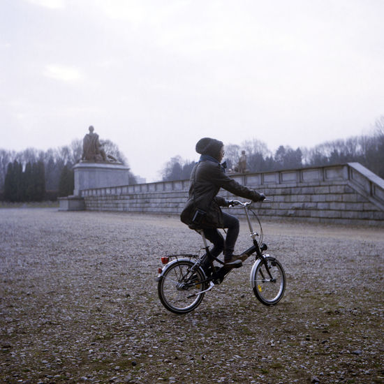 Park alley close to the Soviet Military Cemetery, Warsaw. Soviet Military Cemetery Warsaw Bicycle Cycling Film Photography Filmisnotdead Lifestyles Mausoleum Motion Old Bike One Person Park Riding A Bike  Transportation Vintage Young Adult EyeEmNewHere Shades Of Winter 6x6 #urbanana: The Urban Playground