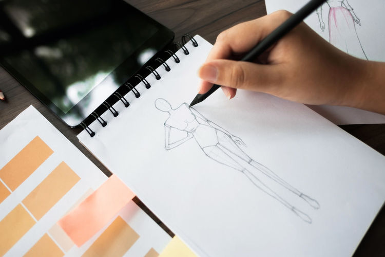 Cropped Hand Of Fashion Designer Drawing Sketch In Office