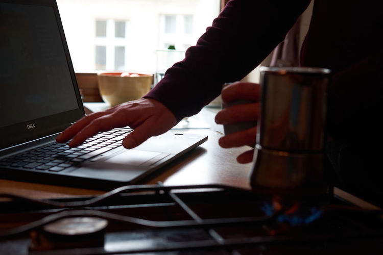 Midsection of person using laptop on table