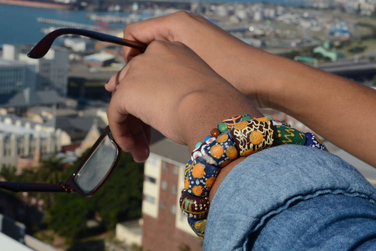 Cropped image of woman holding eyeglasses against city