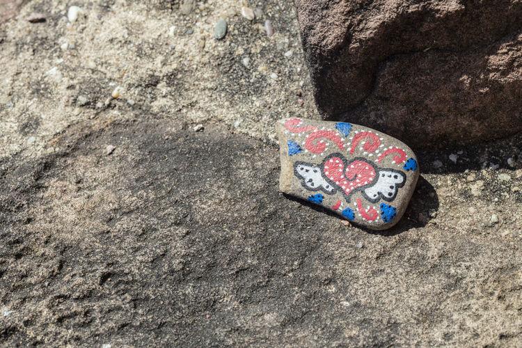 High angle view of heart shape on rock