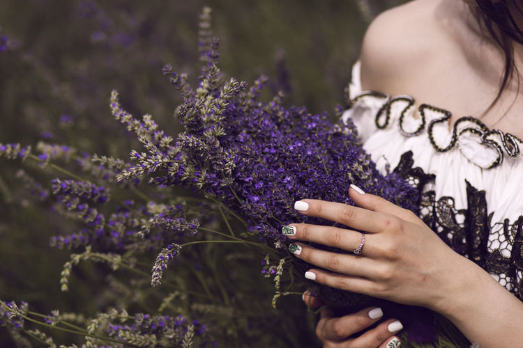 Midsection of woman standing by purple flowering plants