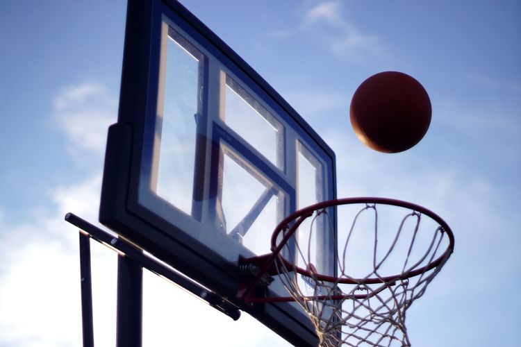 Low angle view of basketball over hoop against sky
