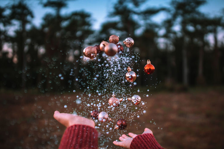 Season of magic. Christmas time.❄🎅🎄. Christmas balls that float on the air. Motion Nature Real People Vintage Tree Bokeh Celebration Day Christmas Hand Outdoors Christmas Lights Christmas Decoration Plant Blowing Throwing  Holding Lifestyles Mid-air Body Part One Person Leisure Activity Focus On Foreground Human Body Part