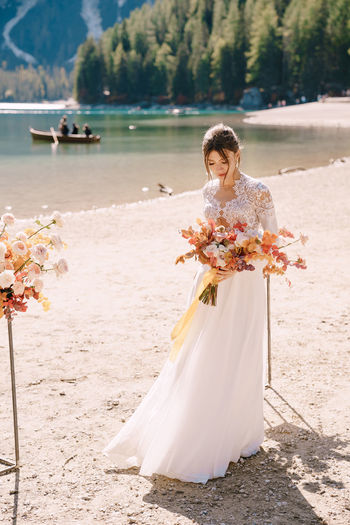 Bride holding bouquet looking away by riverbank