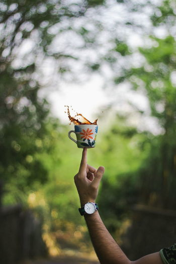Close-up of hand holding tea cup on finger