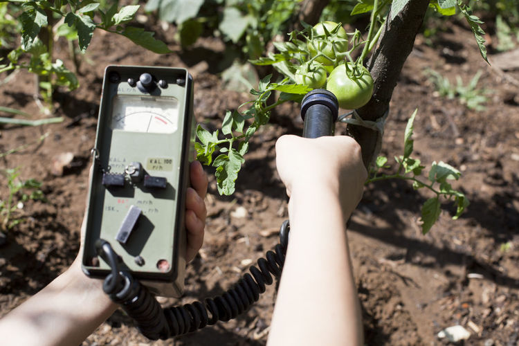 Close-up of woman holding geiger counter on agriculture field