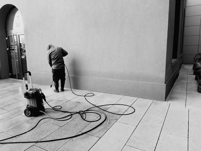 Rear view of man cleaning floor against wall
