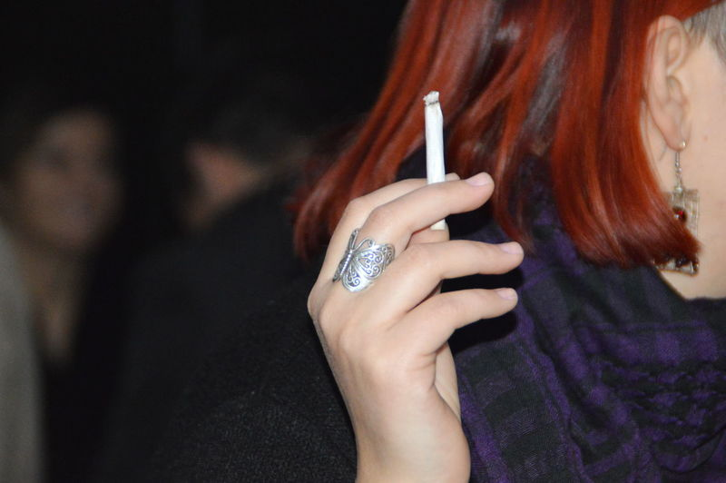 Cropped image of woman wearing ring holding cigarette