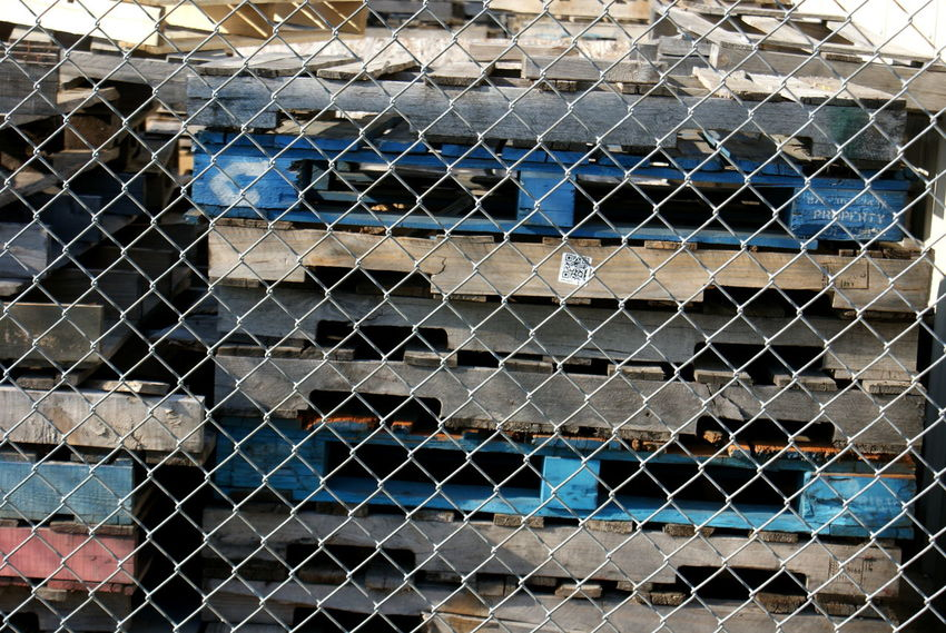 Stacks of used pallets show great textures of old wood in colors of brown, tan, blue and red, making great geometric patterns behind the diagonal metal of a chain link fence. Backgrounds Blue Brown Building Chain Link Fence Chainlink Fence Close-up Construction Day Fence Focus On Foreground Full Frame Metal No People Old Wood Outdoors Pallets Pile Piles Of Wood Red Wood