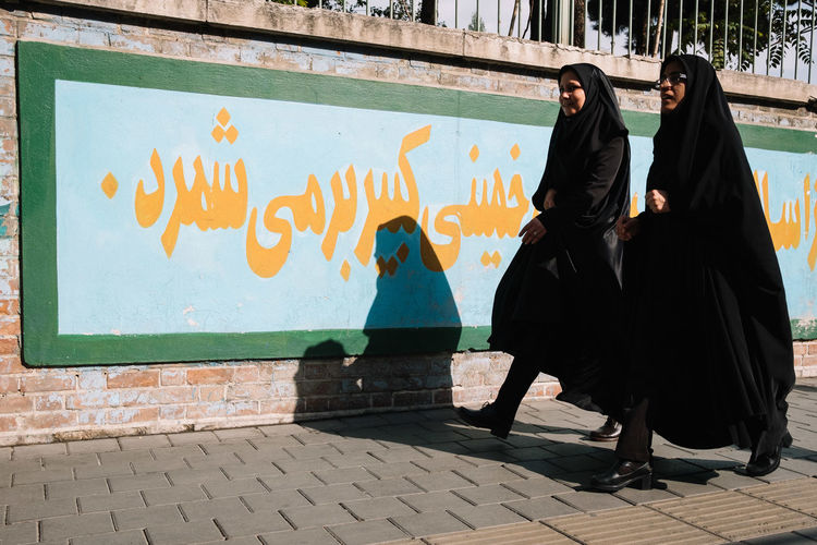 People on footpath against graffiti wall