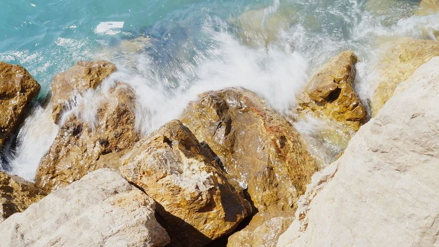 High angle view of rocks by sea during sunny day