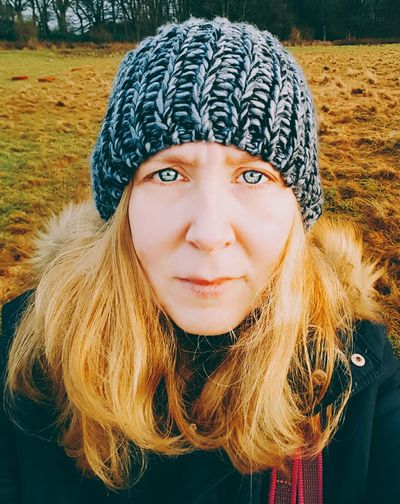 Portrait of woman wearing knit hat while standing on field