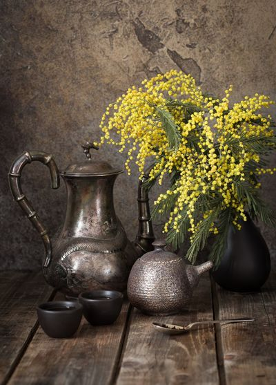 Close-Up Of Yellow Flowers In Vase By Cutlery On Wooden Table