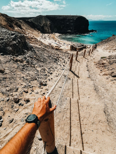 Cropped hand of man on bollard at beach