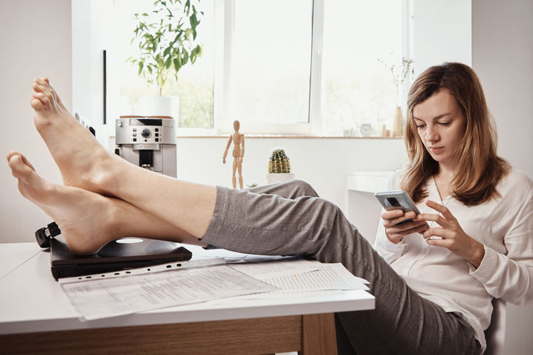 Young woman using smart phone while sitting on laptop