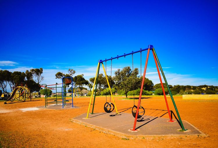Swing at playground against blue sky