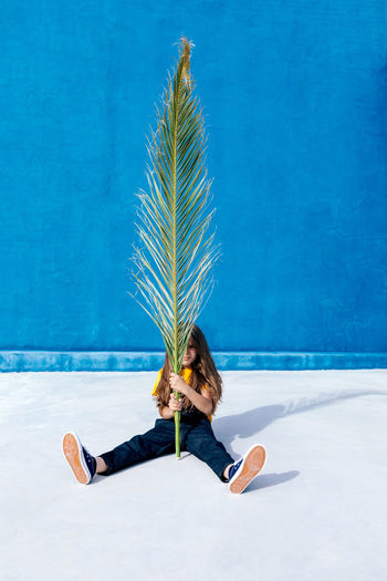 Woman with palm tree in swimming pool
